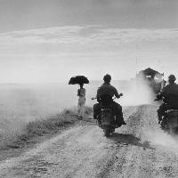 Dei motociclisti e una donna percorrono la strada da Nam Dinh a Thai Binh, Indocina (Vietnam), maggio 1954